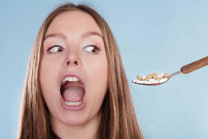 девушка пьёт таблетки от головной боли